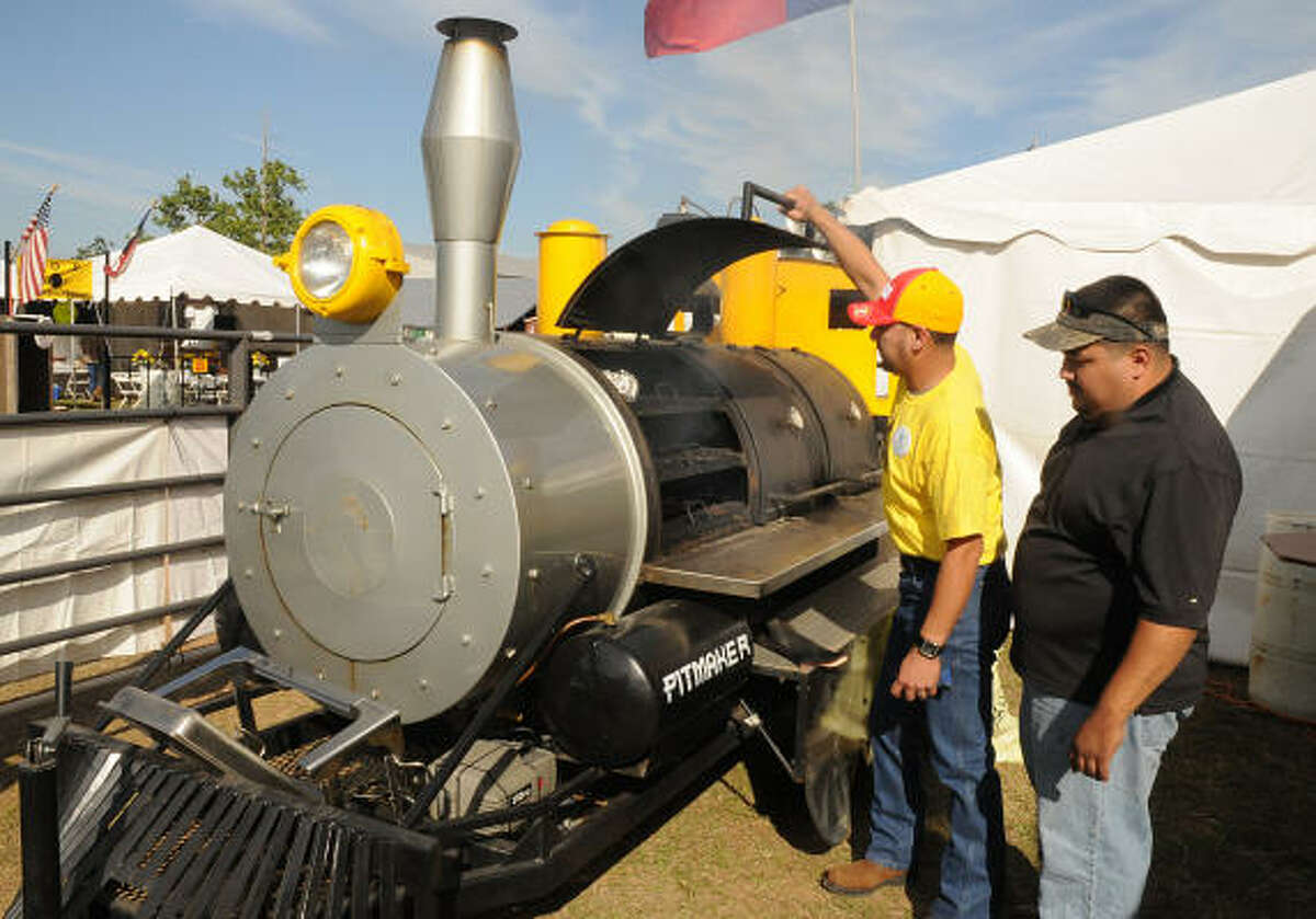 Lupe Garza and John Cisneros, both of Conroe, check the temperature in the train cooker at the Pitmaker booth.