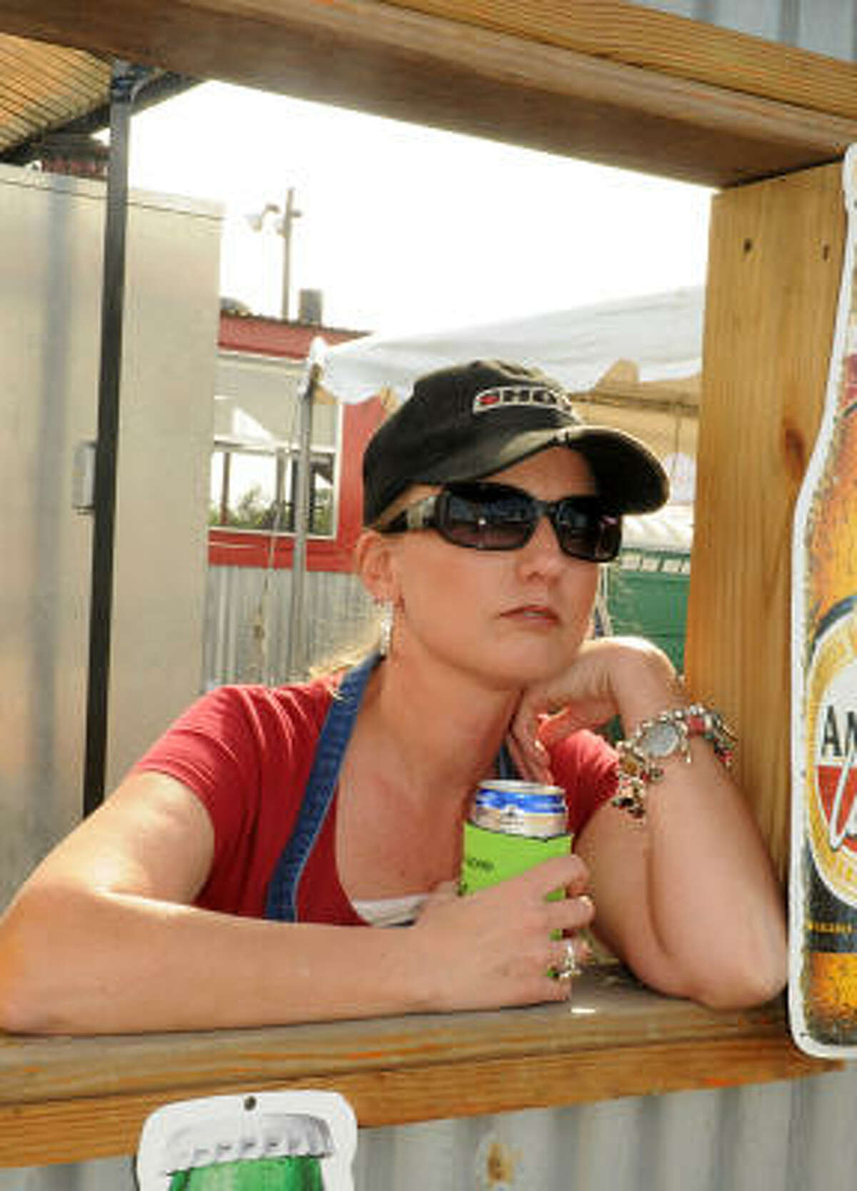 Michelle Risha, of Conroe, watches the crowd from the Porky's Pig Pen booth.