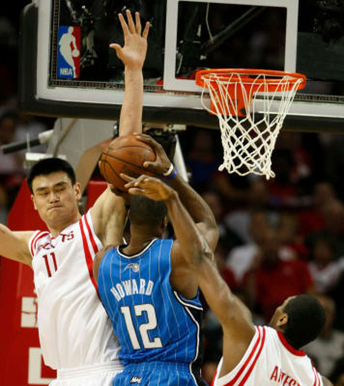Yao Ming (11), left, and forward Ron Artest (96) cover up Magic center Dwight Howard (12) on a play in the paint in the third quarter.