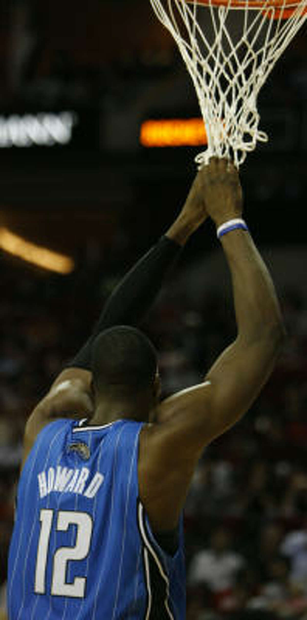 Magic center Dwight Howard (12) hangs on the net during a timeout in the fourth quarter.