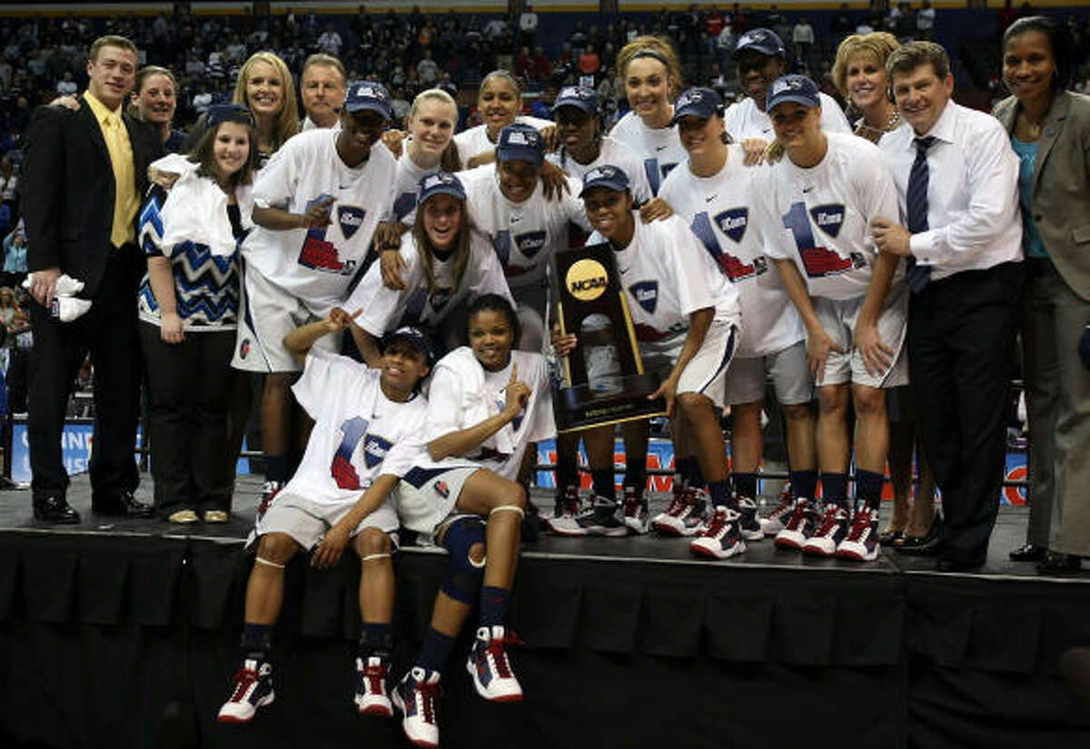 The Connecticut Huskies pose with the championship trophy during the NCAA Women's Final Four at the Scottrade Center in St. Louis.