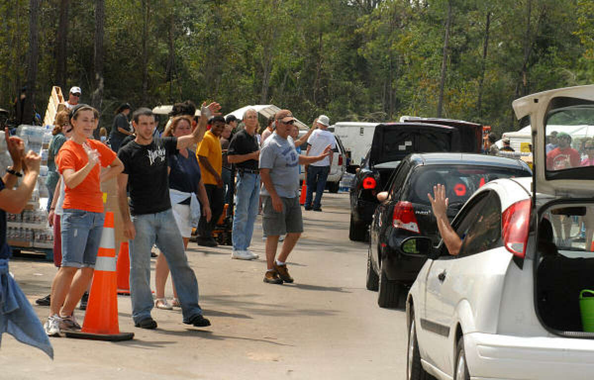 Kylie Phillips and Andrew Barton, of The Woodlands, smile and wave as cars pull into the POD.