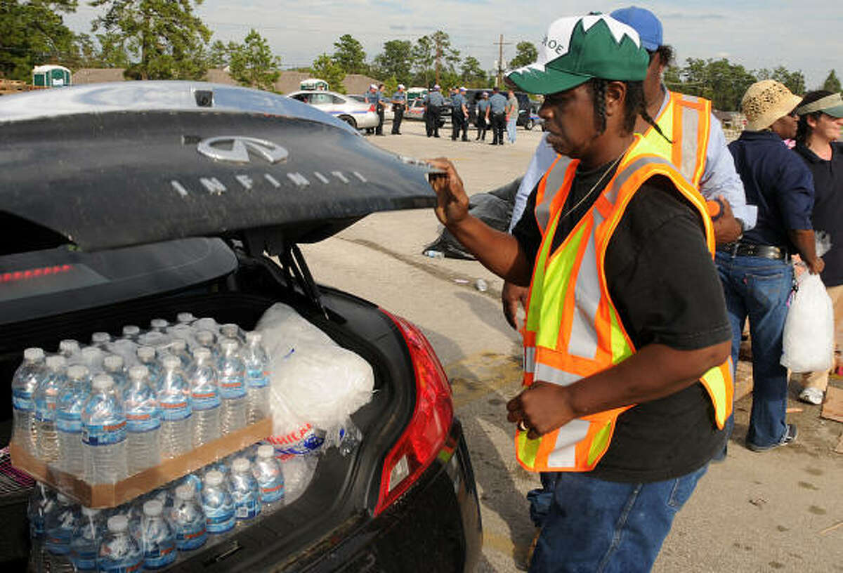 Volunteer Ruby Johnson closes the trunk of a car at the Conroe High School POD, after placing water and ice in the trunk.