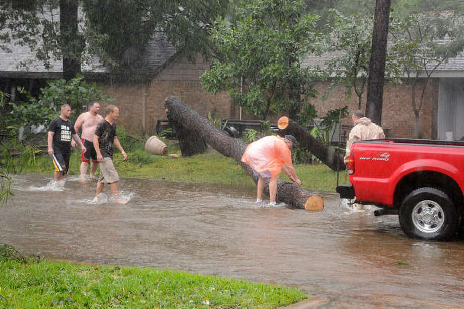 Neighbors banded together during Hurricane Ike to remove one of the two trees that fell across Tickner St. near Erickson St. in Conroe. The trees were blocking the street and one neighbor used a chainsaw to help remove it from the road. Photo: David Hopper, For The Chronicle