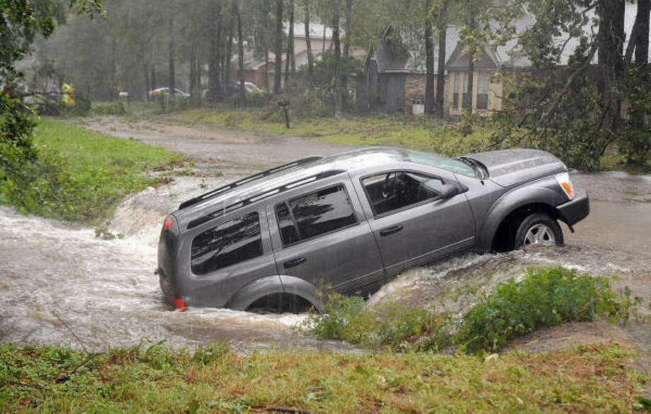 A driver and her infant were pulled from their SUV by residents on Hancock St, near Tickner St., in Conroe after she accidently backed her car into a creek while trying to turn around to avoid a fallen tree in the street. Photo: David Hopper, For The Chronicle