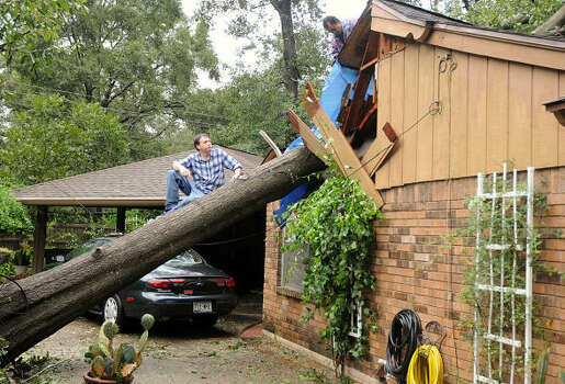 Sam Wilkinson sits in a tree that crashed into his mother's house, on Lilly Street near Thompson street, in Conroe. Wilkinson's mother was cooking when she heard a noise and saw the tree falling. She ran, and the tree crashed through the roof and landed on the stove where she had been cooking. Photo: David Hopper, For The Chronicle