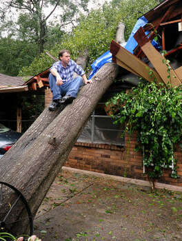 Sam Wilkinson sits on the tree that crashed into his mother's home, on Lilly Street near Thompson Street, in Conroe. The tree crashed into the kitchen and barely mised hitting his mother. Photo: David Hopper, For The Chronicle
