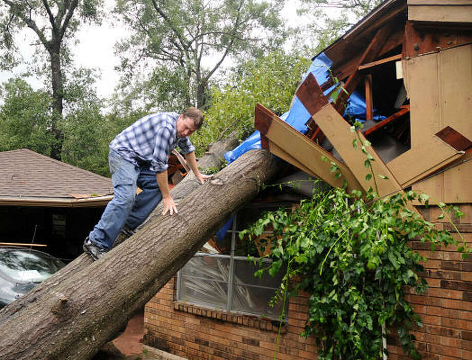Sam Wilkinson climbs the tree that crashed into his mother's home. Wilkinson was covering the hole with plastic until the home can be fixed. Photo: David Hopper, For The Chronicle