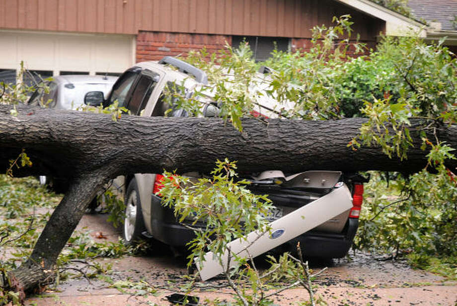 A crushed SUV sits in the driveway of a house, on Wilson Road near Frazier Street, in Conroe. The tree not only crushed the SUV, but blocked the other car from getting out of the driveway. Photo: David Hopper, For The Chronicle