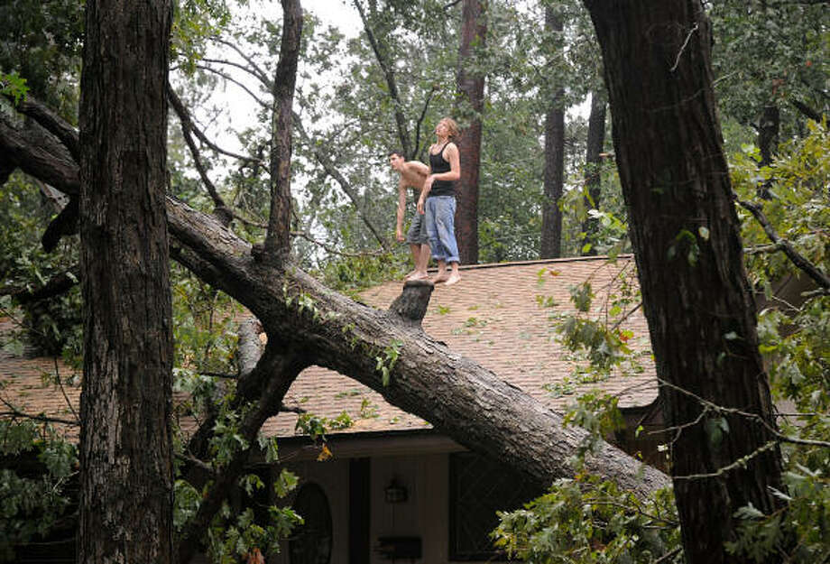 Residents try to get a bird's eye view of the damage to their house caused by a tree falling on the roof of their N. Thompson, near Lilly Blvd, home in Conroe. Photo: David Hopper, For The Chronicle