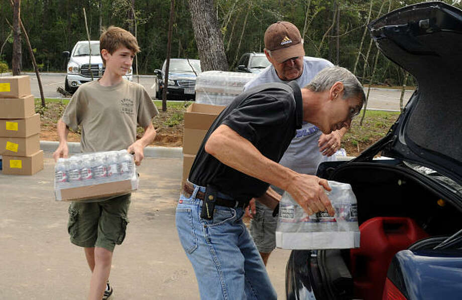 Tom Reed, of The Woodlands, places ice in the trunk as his son Ryan brings water to the car. Reed and four of his children volunteered at the Fellowship of The Woodlands Church POD. Photo: David Hopper, For The Chronicle