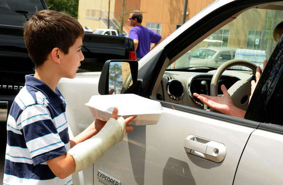 Roman Dontrelepont, of The Woodlands, hands a meal, broken arm and all, to a driver at the Fellowship of The Woodlands Church POD. Photo: David Hopper, For The Chronicle