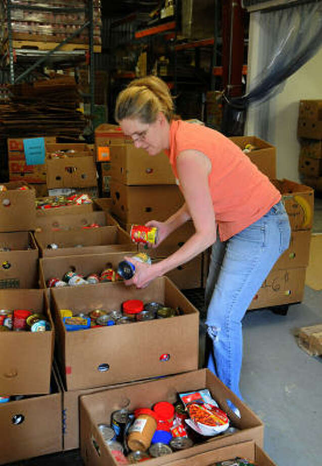 Volunteer Kellye Goleman, of Cut and Shoot, places canned goods in a box at Montgomery County Food Bank. Photo: David Hopper, For The Chronicle