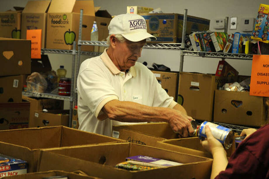 Volunteer Don Earnest, of Montgomery Methodist Church, places canned goods in a box at the Montgomery County Food Bank. Photo: David Hopper, For The Chronicle