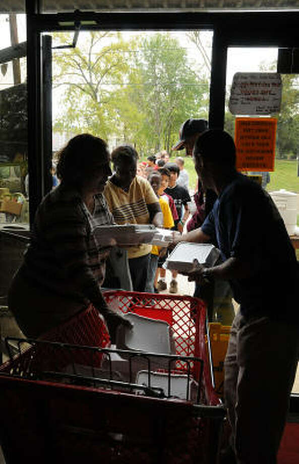 Volunteers Angella Bollard and Jim Ethridge hand out meals to storm victims at the Montgomery County Salvation Army, Avenue E and 1st Street in Conroe. Photo: David Hopper, For The Chronicle