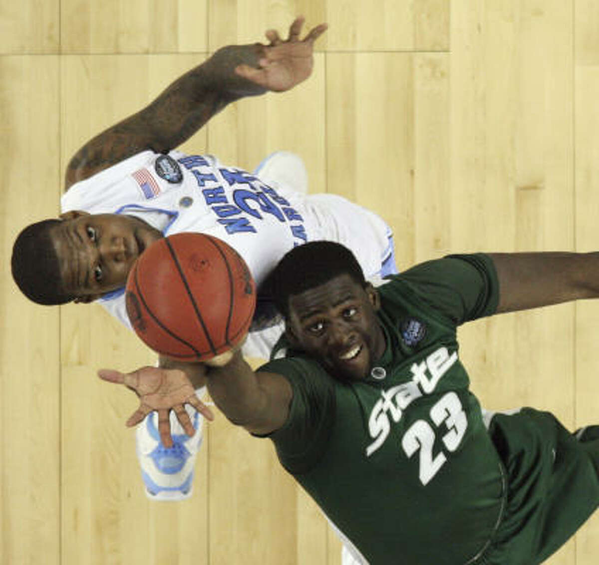 North Carolina's Deon Thompson (21) and Michigan State's Draymond Green (23) go for a rebound.