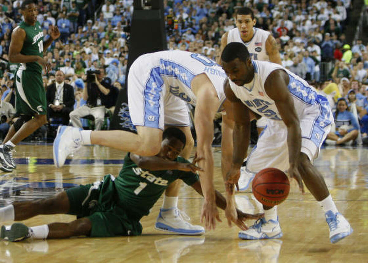 North Carolina's Tyler Hansbrough, top, Ty Lawson (5), and Michigan State's Kalin Lucas (1) scramble for a loose ball.