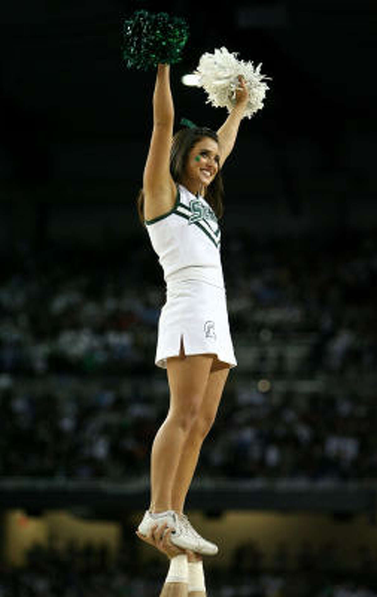 A cheerleadeer for the Michigan State Spartans performs against the North Carolina Tar Heels.