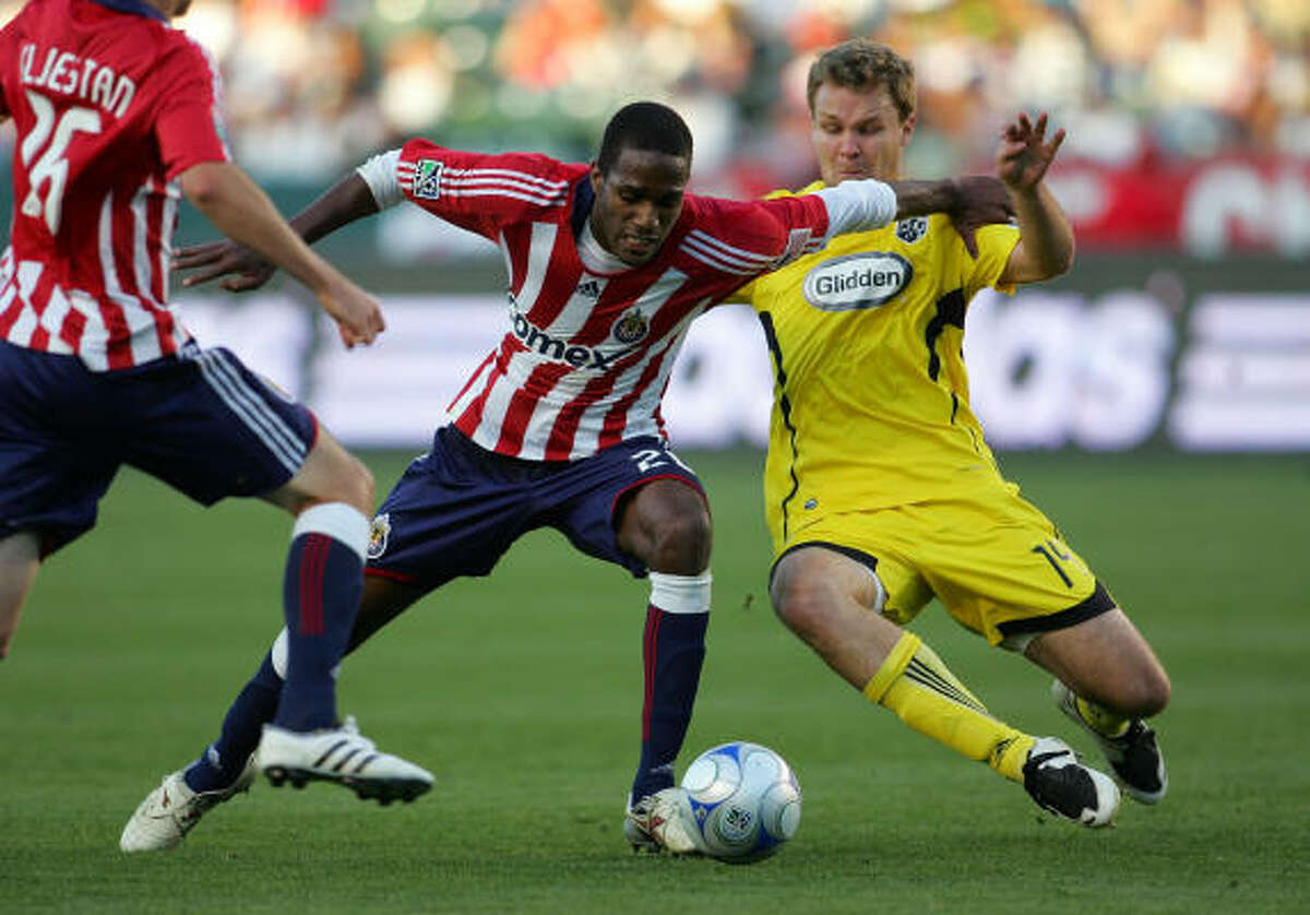 Chad Marshall of Columbus Crew slides in for the tackle against Atiba Harris of Chivas USA.