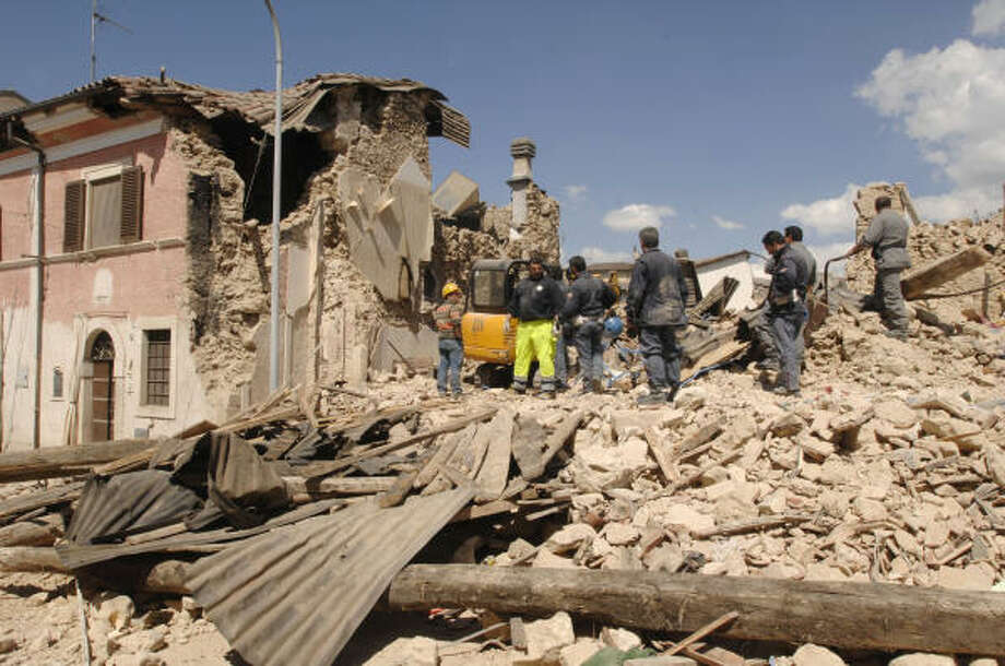 Rescuers and volunteers remove debris in the village of Onna. Photo: SANDRO PEROZZI, AP