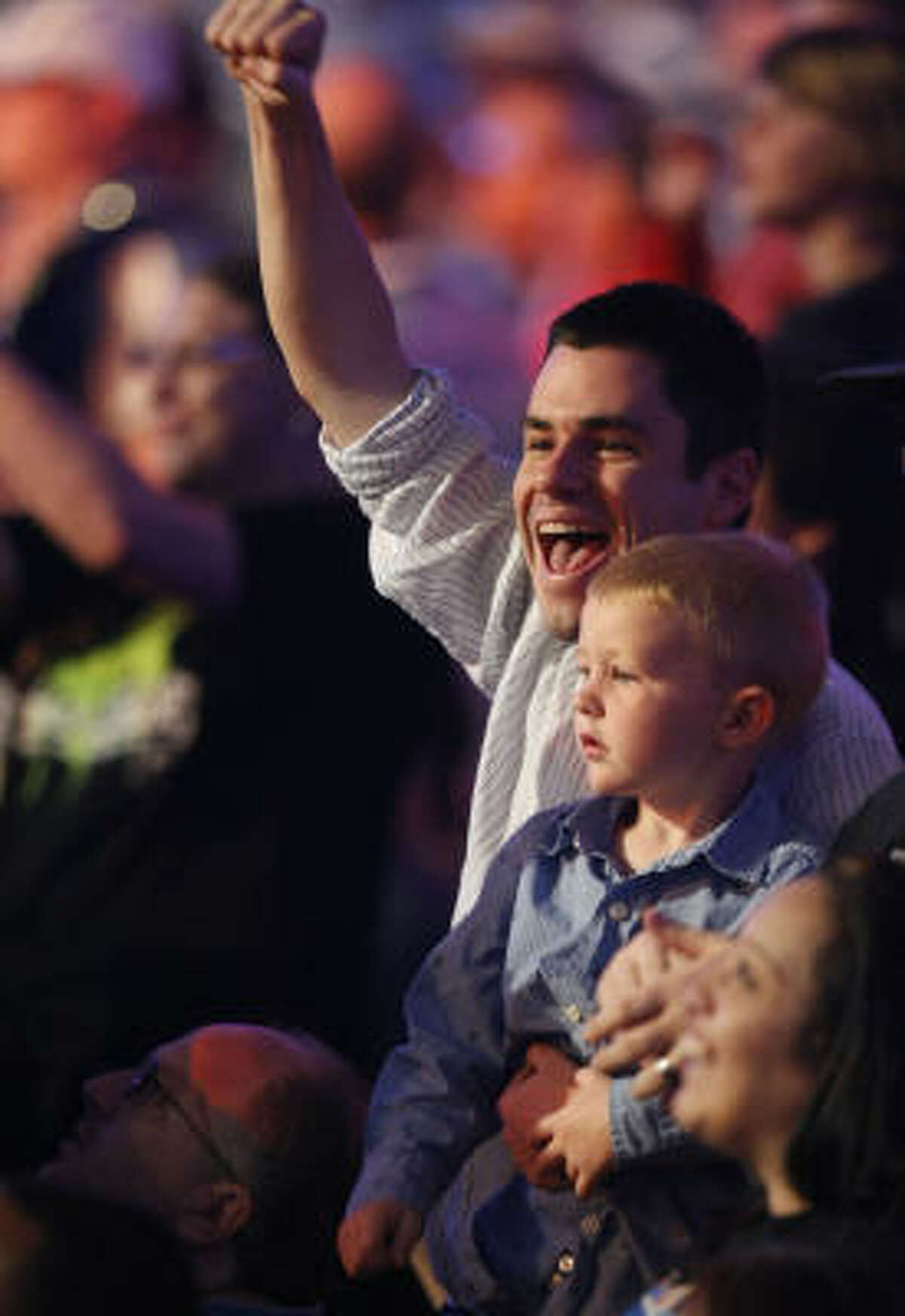 Andrew Herbert, 26, top, and his son Jacob Herbert, 5, sing along to the song Cowboy by recording artist Kid Rock during the 25th anniversary of Wrestlemania held at Reliant Stadium.