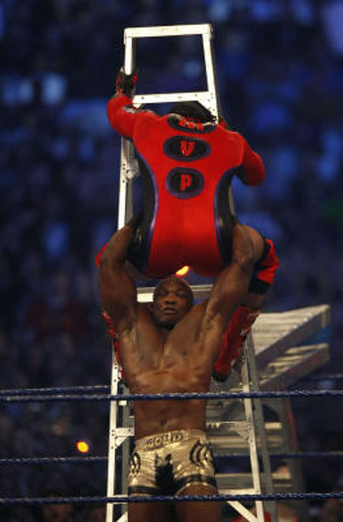 WWE wrestler Shelton Benjamin, also known as Gold Standard, bottom, brings down MVP during the Money in the Bank Ladder Match during the 25th anniversary of Wrestlemania.