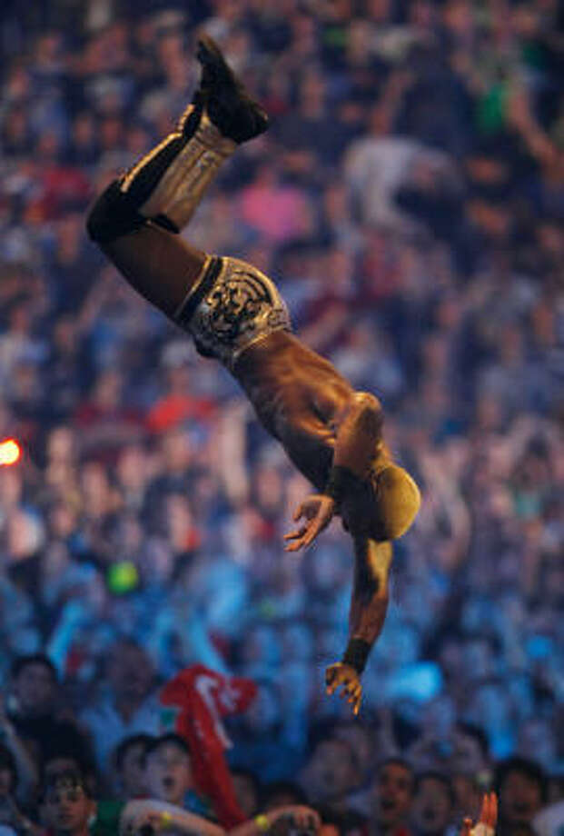 Shelton Benjamin performs a moonsault off a ladder and outside of the ring at Wrestlemania 25 in Houston. Photo: Julio Cortez, Chronicle