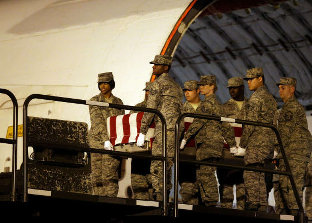 Members of the U.S. Air Force carry team transports a transfer case holding the remains of Air Force Staff Sgt. Phillip Meyers of Hopewell, Va. during an arrival ceremony at Dover Air Force Base,in Dover, Delaware.
