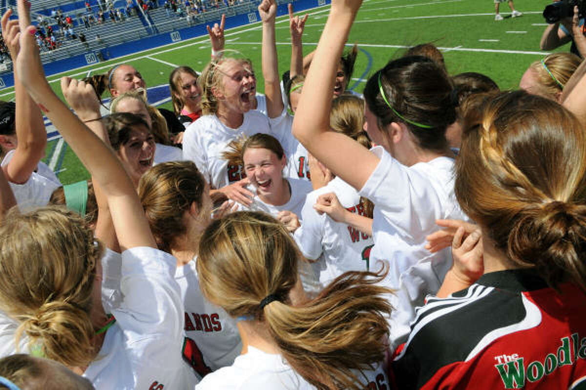 The Woodlands senior midfielder Kelsey Bass, center, finds herself in the middle of the Lady Highlander's celebration after their 2-1 win over Cy-Creek in the Region II-5A tournament final on Birklebach Field at the Georgetown Independent School District Athletic Complex on Saturday.