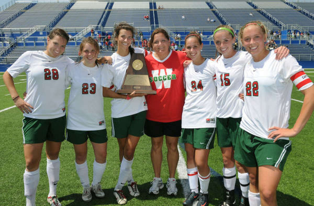 The Woodlands girls head soccer coach Dina Graves, center, and her captains Meghan Gibbons, from left, Kelsey Bass, Kylie Cook, Teresa Sorrentino, Molly Missimer and Olivia Kintigh celebrate their first-ever regional championship after defeating Cy-Creek 2-1 on Birklebach Field at the Georgetown Independent School District Athletic Complex on Saturday.