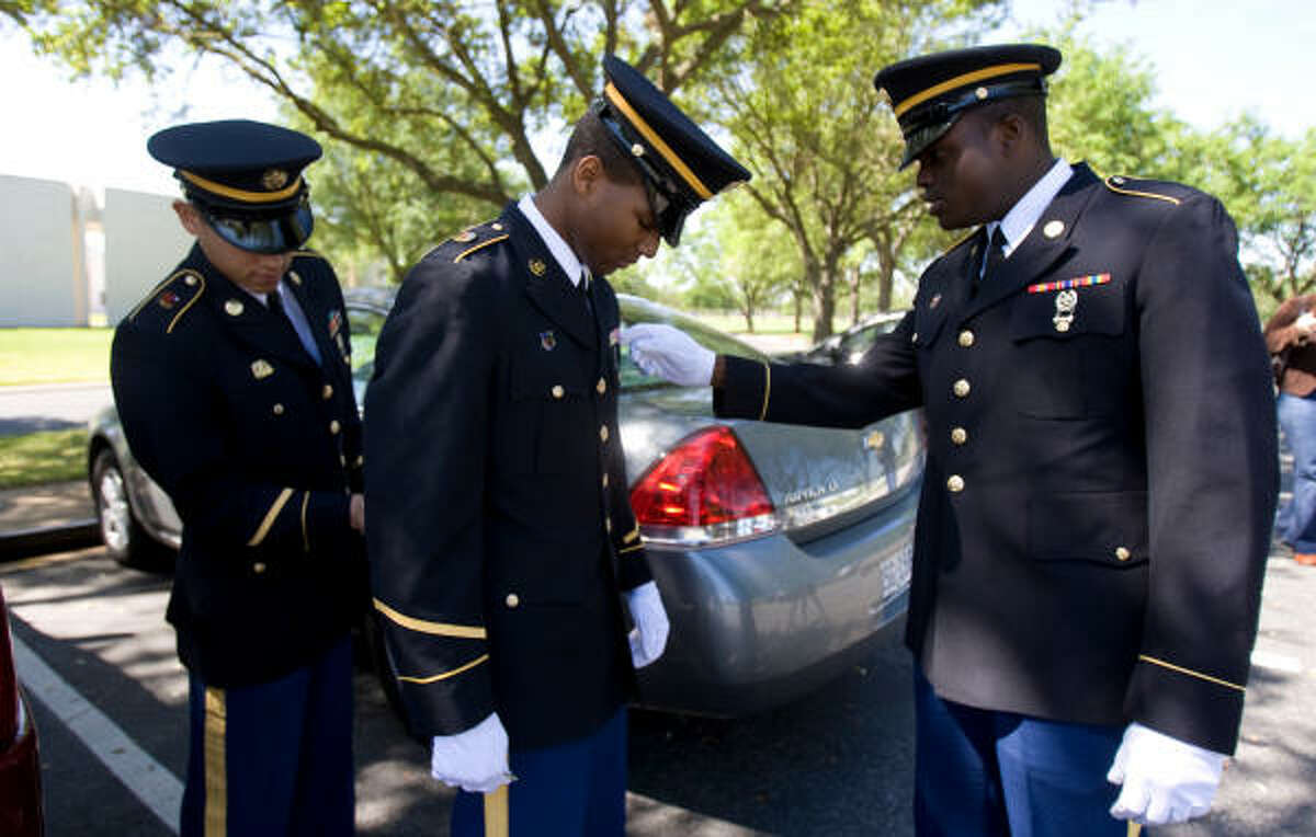 Texas National Guard Specialist Jermaine Hunt, center, stands still as Spc. Joshua Contreras and Pvt. Eric Wiliams primp his uniform before the honor guard team serve a funeral at the Houston National Cemetery in Houston.