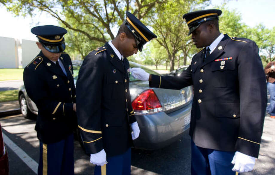 Texas National Guard Specialist Jermaine Hunt, center, stands still as Spc. Joshua Contreras and Pvt. Eric Wiliams primp his uniform before the honor guard team serve a funeral at the Houston National Cemetery in Houston. Photo: Nick De La Torre, Houston Chronicle