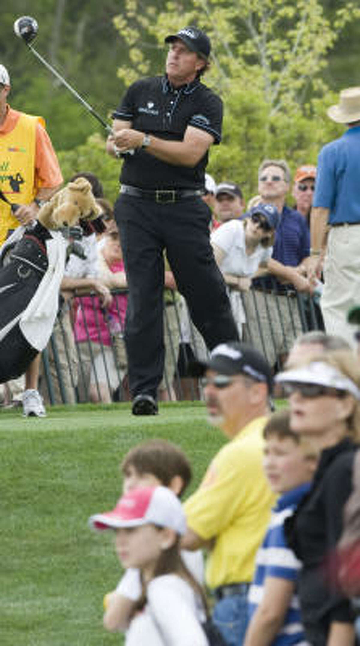 Phil Mickelson watches his tee shot on No. 18 during the second round. He made par on the hole to finish the round at 4 over.
