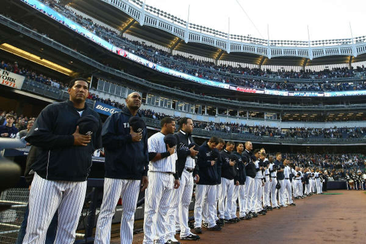 NEW YORK - APRIL 03: New York Yankees players wait for the playing of the national anthem prior to the start of their game againstthe Chicago Cubs on April 3, 2009 at Yankee Stadium in the Bronx borough of New York City. The exhibition game is the first game to be played at the new Yankee Stadium.