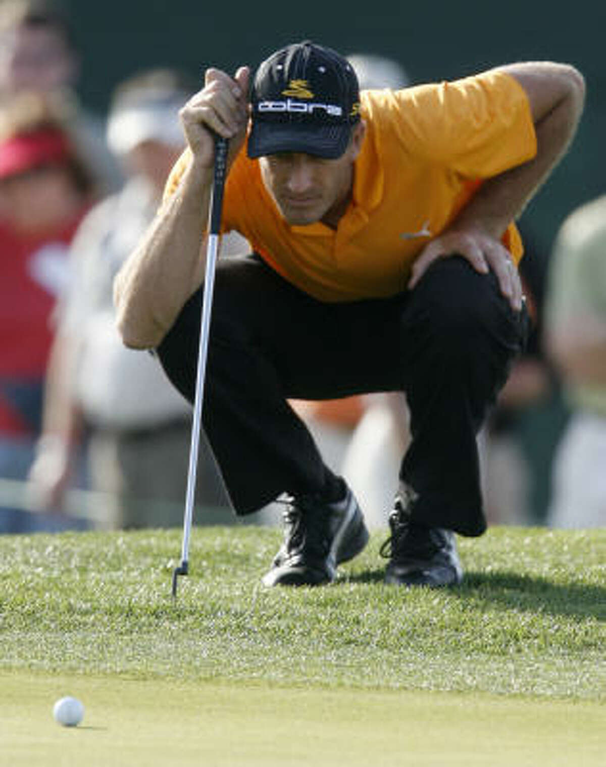 Geoff Ogilvy lines up a putt on the 17th hole during the delayed second round.