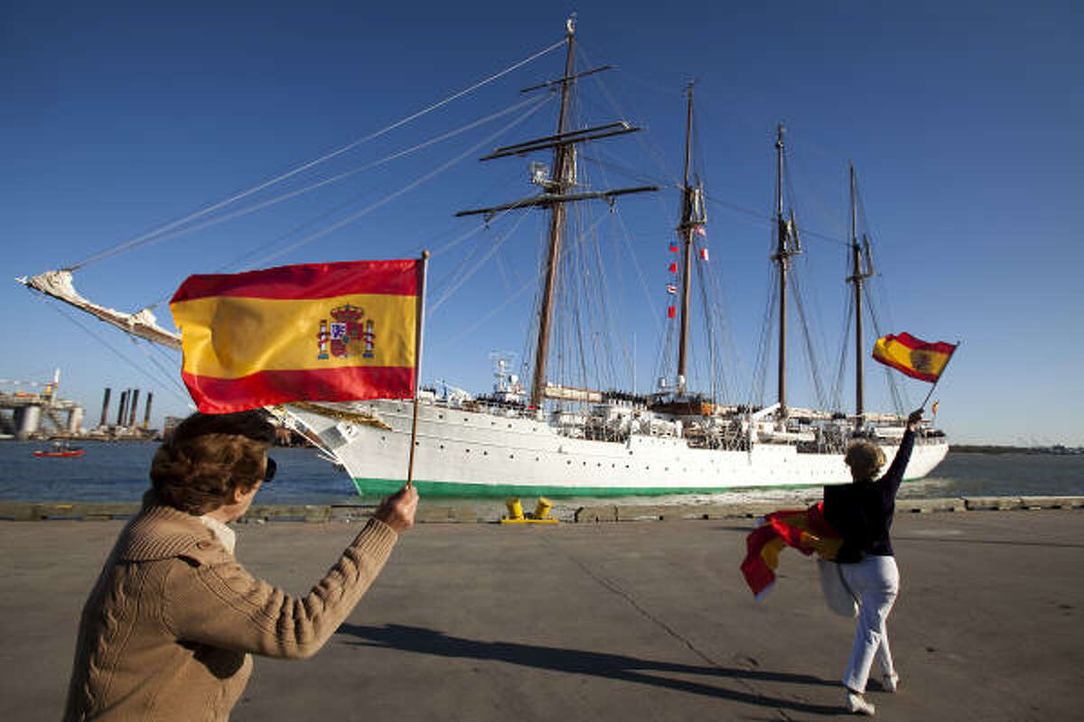 Uca Agullo, left, and Maria Romero, right, wave Spanish flags as the Tall Ship Juan Sebastián de Elcano arrives.