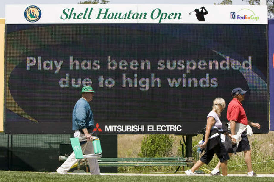 Golf fans walk off the course as play was suspended because of high winds during the first round at Redstone Golf Club. Photo: Brett Coomer, Chronicle