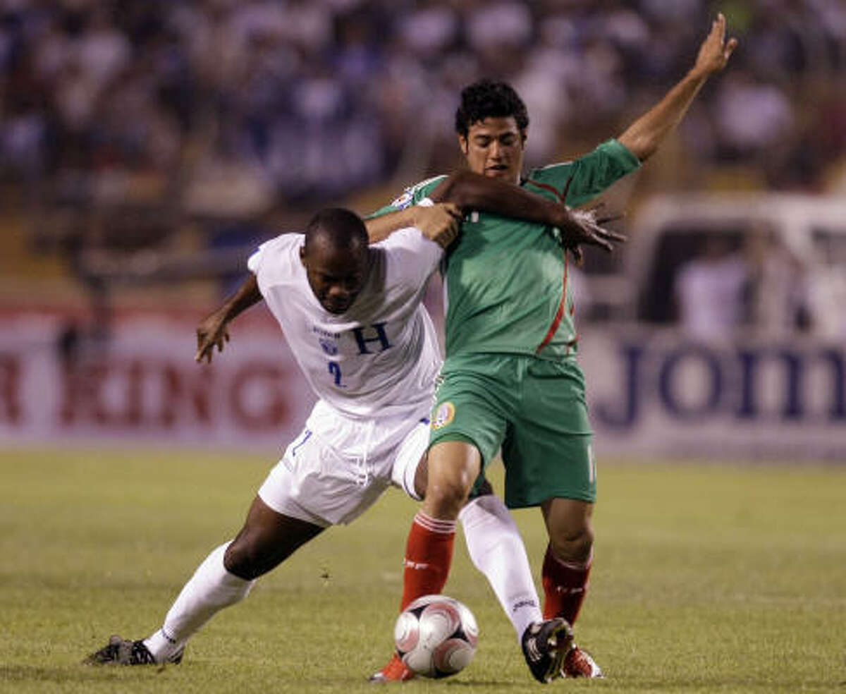 Honduras 3, Mexico 1 Honduras' Jose Magallon, left, and Mexico's Carlos Vela battle for the ball in San Pedro Sula, Honduras.