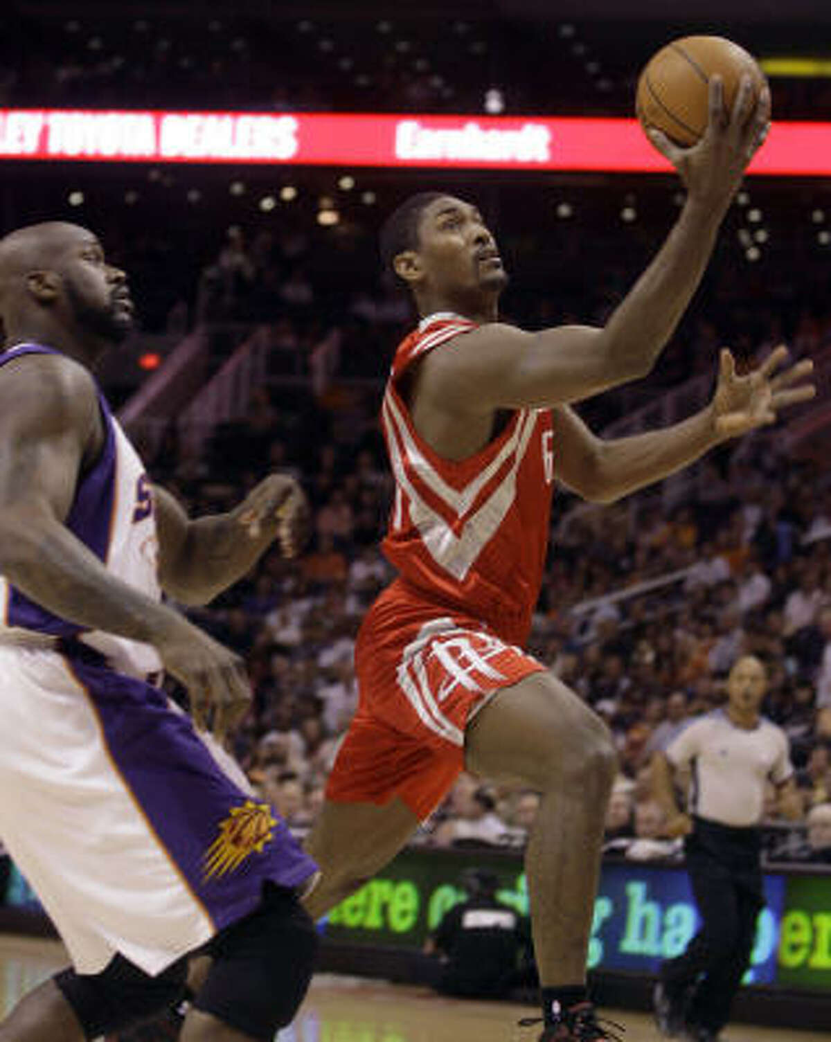Rockets forward Ron Artest, right, drives to the basket past Phoenix Suns center Shaquille O'Neal, left, in the first quarter.