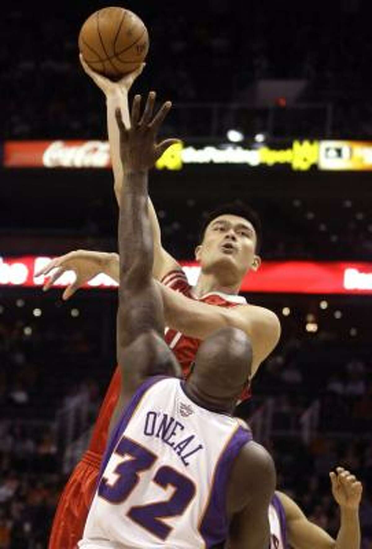 Rockets center Yao Ming, top, shoots over Phoenix Suns center Shaquille O'Neal (32) in the first quarter.