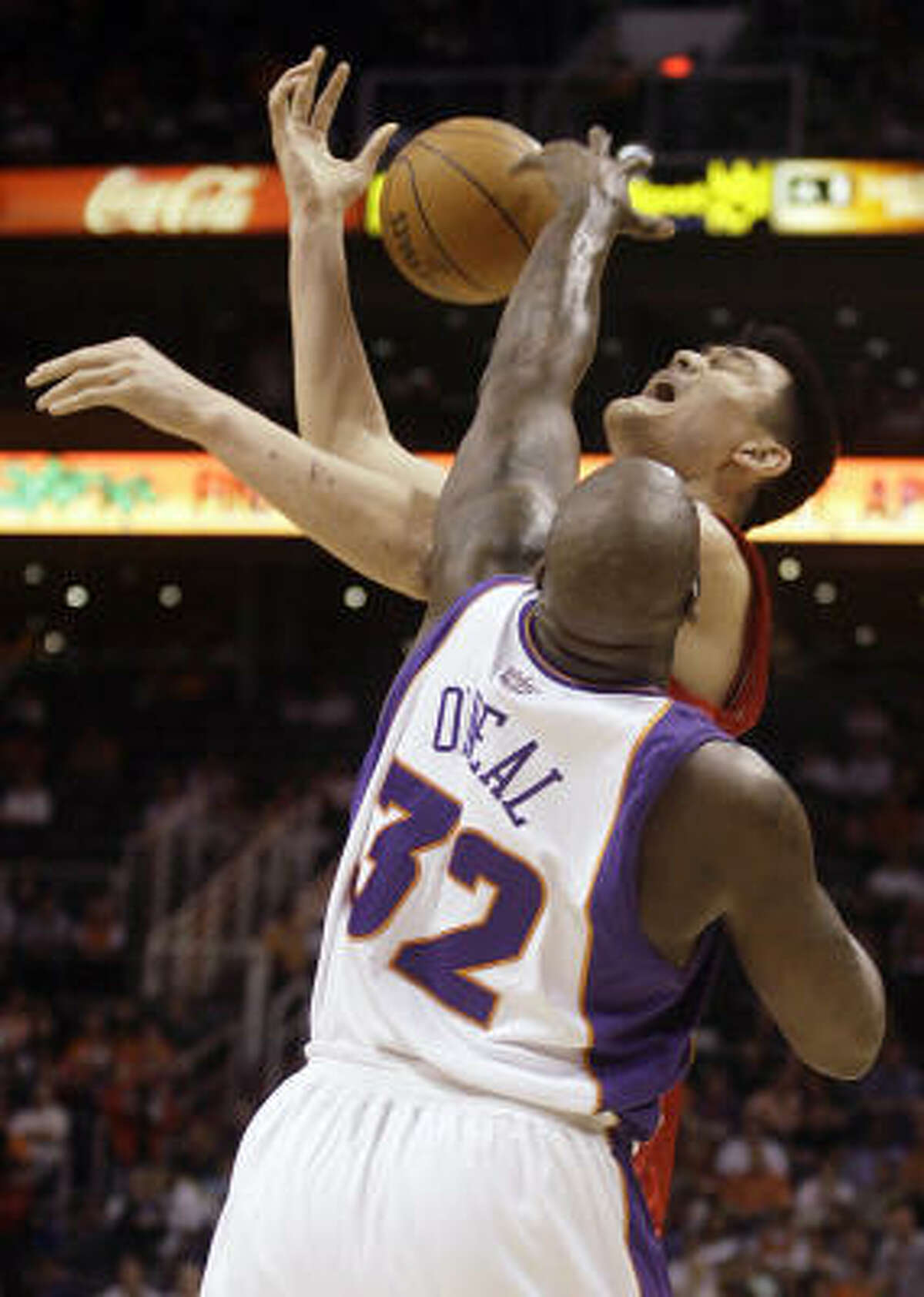Yao Ming is fouled by Phoenix Suns center Shaquille O'Neal, bottom, as he attempts to shoot in the first quarter.