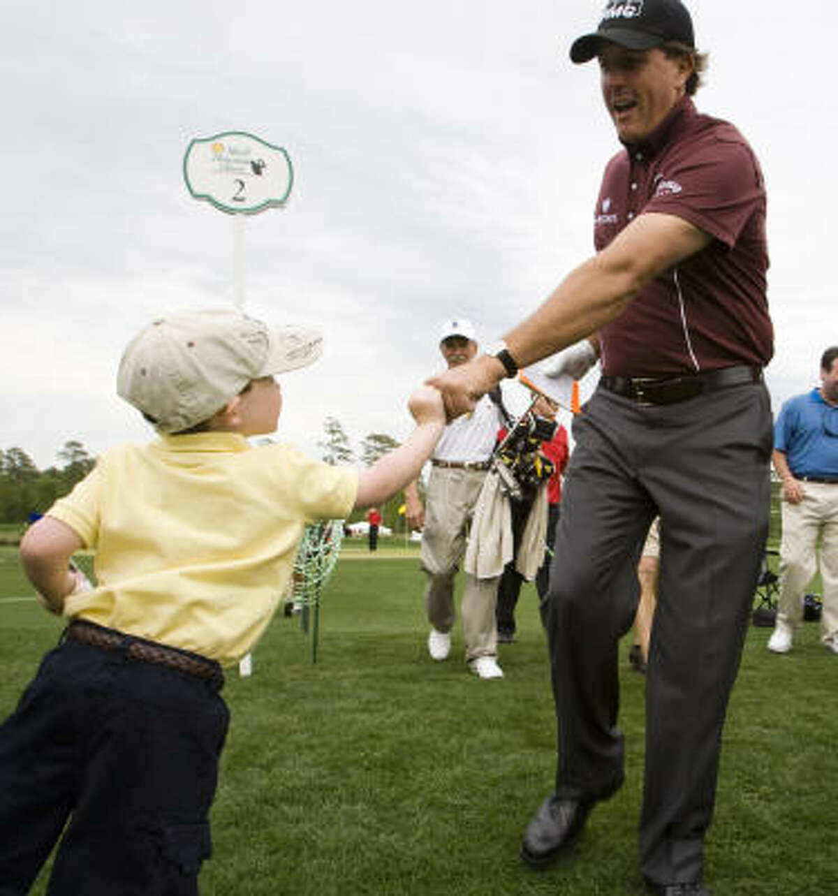 Colin Doran, 4, of Tomball, bumps fists with Phil Mickelson as Mickelson comes off the No. 2 green.