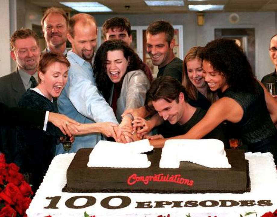 Cast members, front row from left, Laura Innes, Anthony Edwards, Julianna Margulies, George Clooney, Noah Wyle, Kellie Martin and Gloria Reuben, cut a cake celebrating the 100th episode of ER. Photo: RENE MACURA, AP