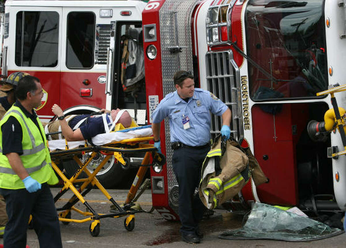 Houston EMS wheels away an injured firefighter.