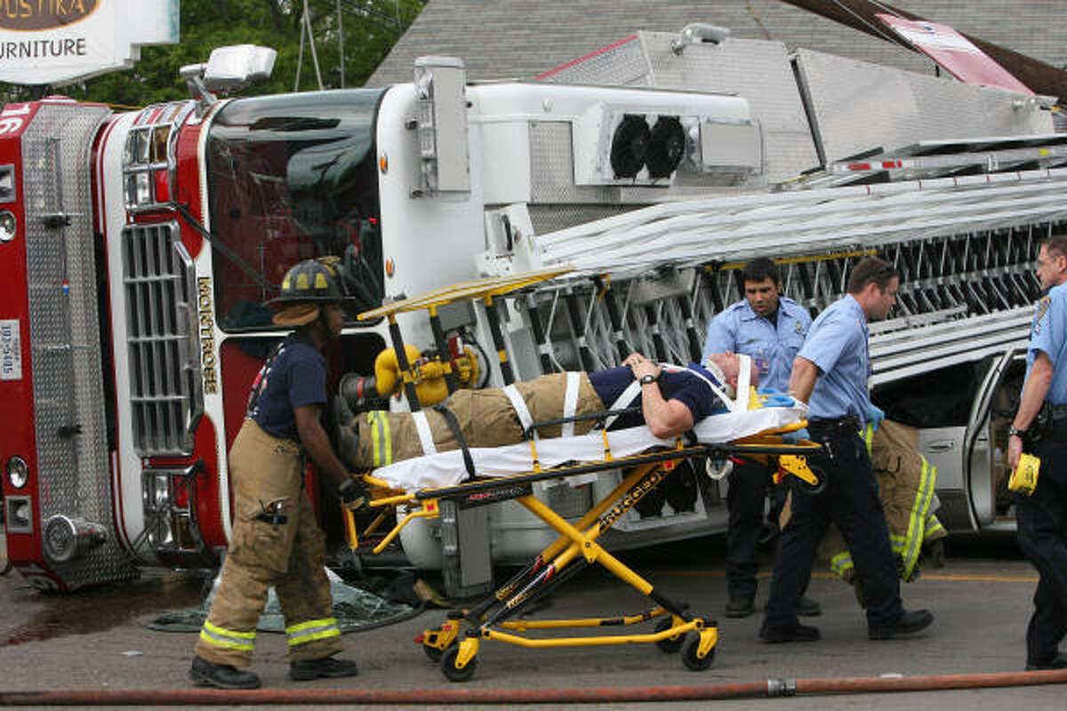 An injured firefighter is carried away on a stretcher.