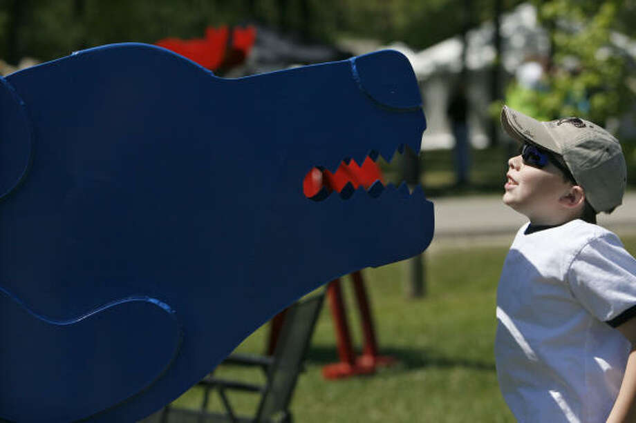 Logan Conchola, 7, of Houston, gets a close look at a sculpture of a bear created by Fred Prescott from Santa Fe, N.M. at the 12th Annual Bayou City Art Festival at Memorial Park. Photo: Johnny Hanson, Chronicle