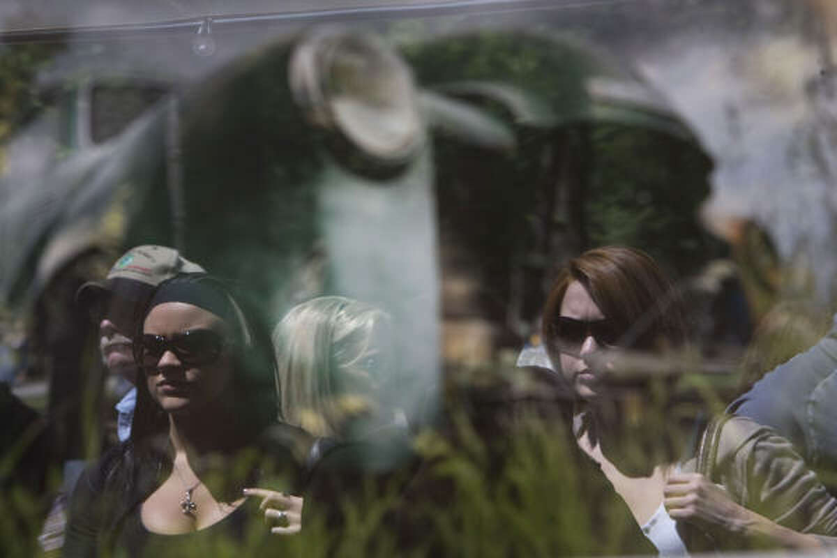 Connie Stewart, 25, of Tomball (left) and Lauren Wolff, 22, (right) of Spring, are reflected in a photograph of a car at the Photoanarchy booth with photography from Mark and Stephen Zurek from Boulder, Colo.