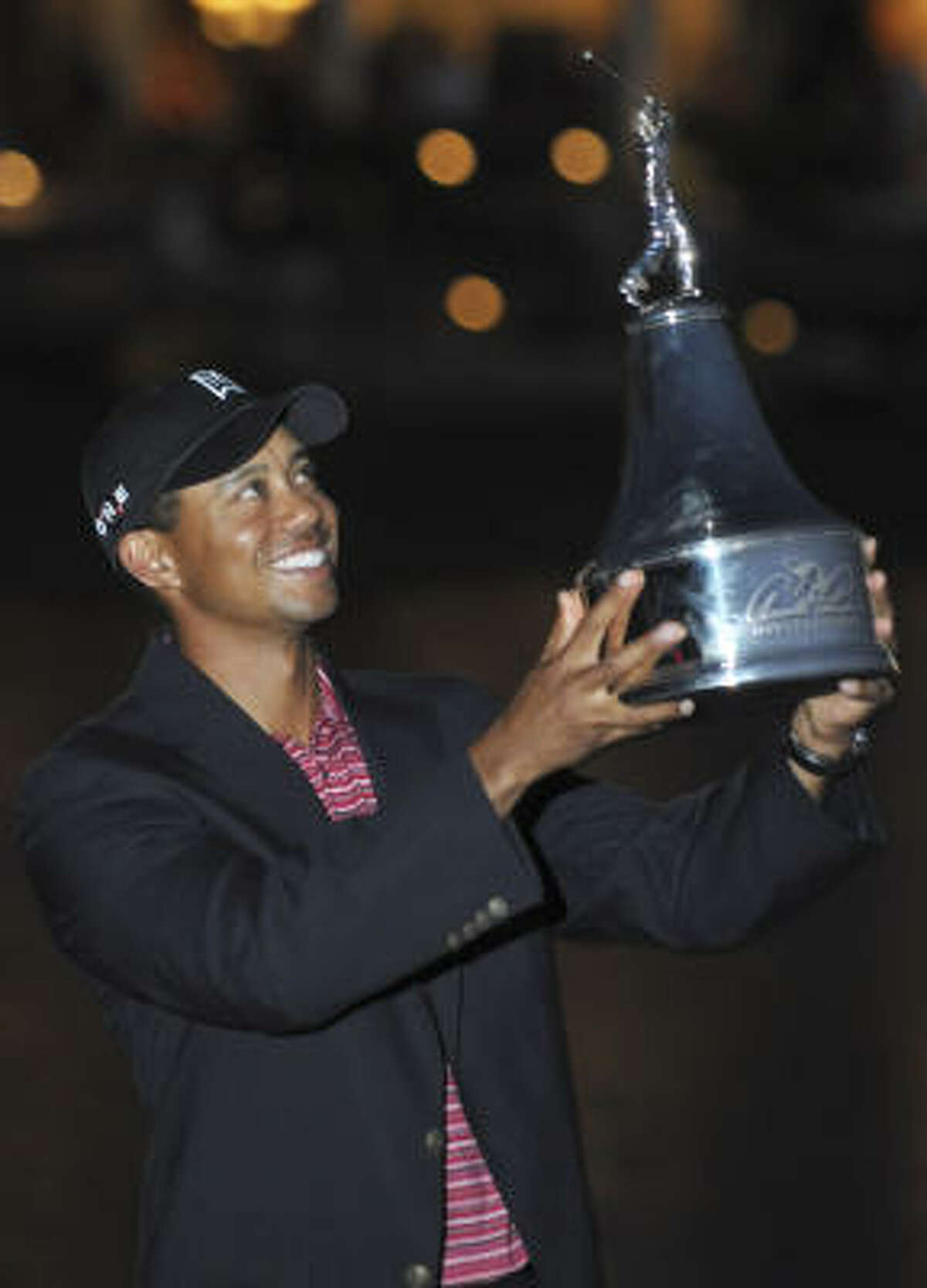Tiger Woods lifts the trophy for winning the Arnold Palmer Invitational at Bay Hill in Orlando, Fla. Woods closed with a 3-under 67 for a one-shot victory over Sean O'Hair.