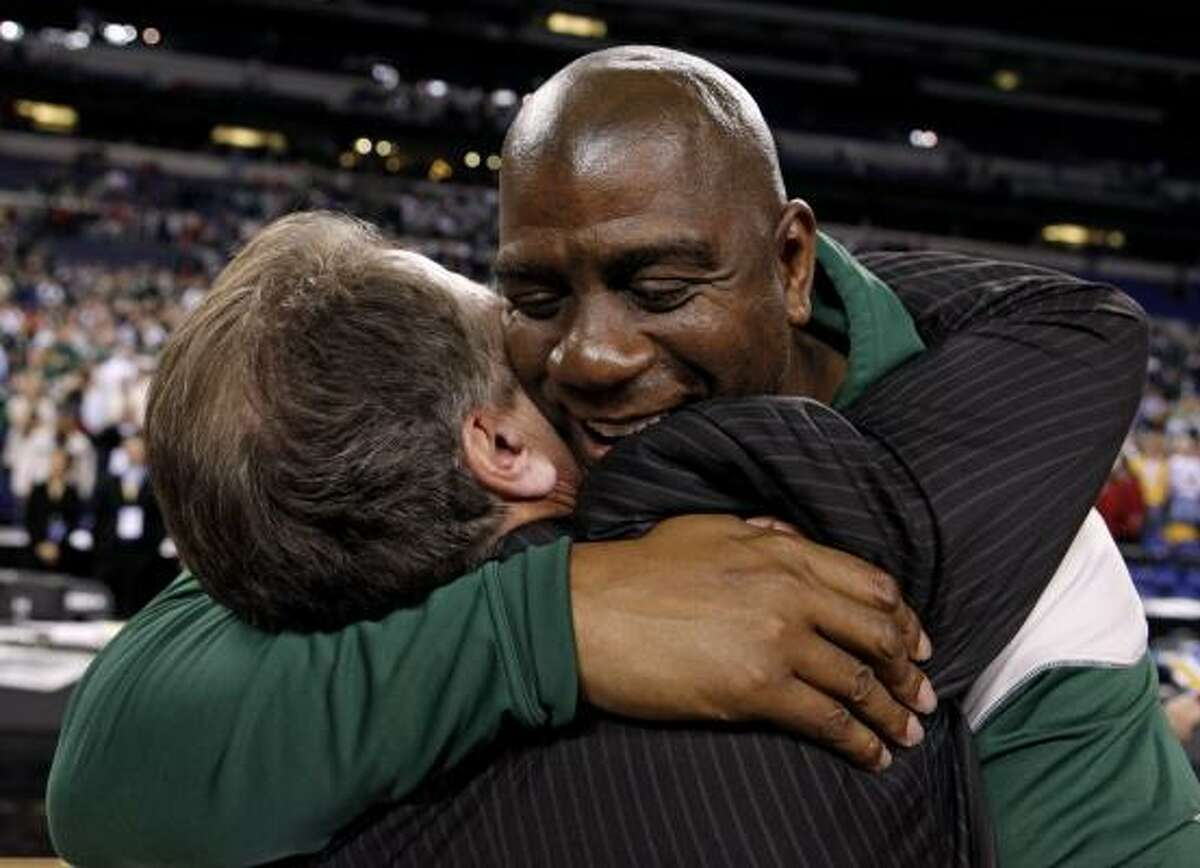 Midwest Region: Michigan State 64, Louisville 52 Former Michigan State player Magic Johnson, right, hugs coach Tom Izzo after Michigan State beat Louisville 64-52.