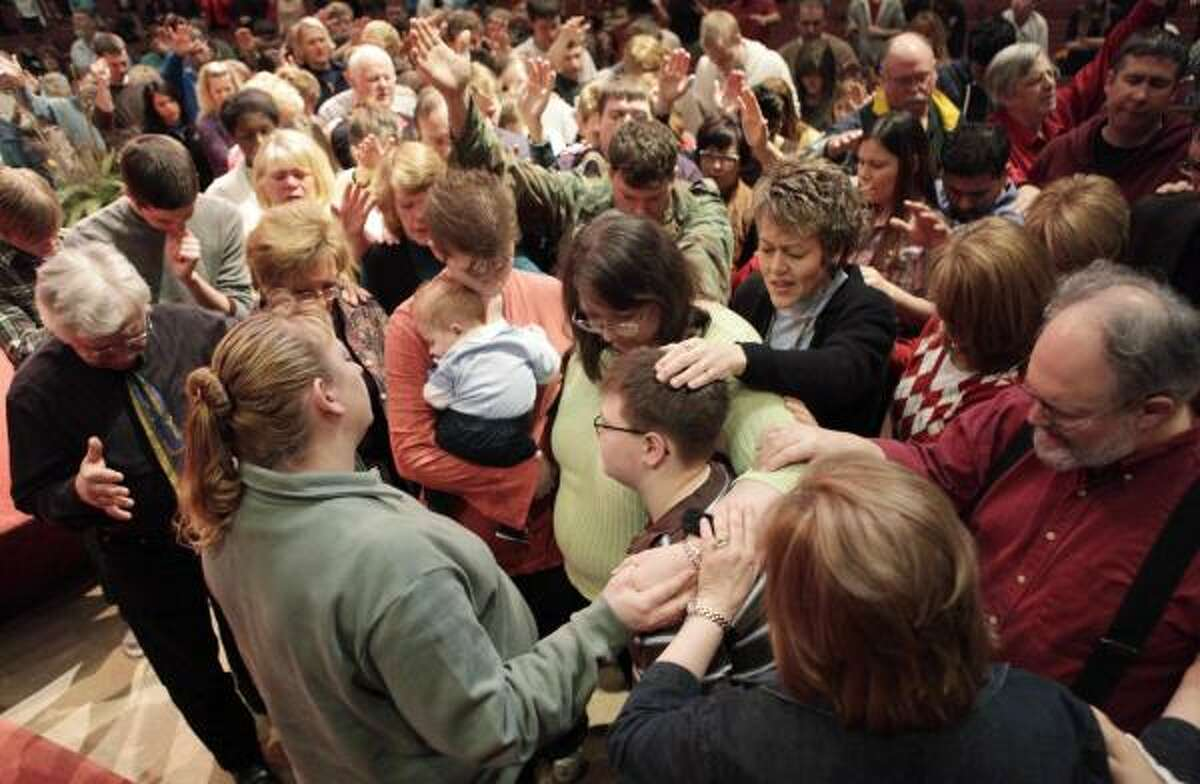 Members of the First Assembly of God church in Fargo, N.D., pray for people who have been affected by Red River flooding Sunday.